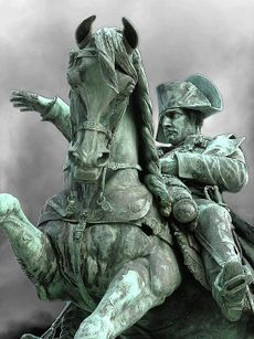 Photo of a grey and phosphorous-coloured equestrian statue. Napoleon is seated on the horse, which is rearing up, he looks forward with his right hand raised and pointing forward; his left hand holds the reins.