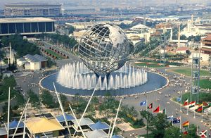 A spherical sculpture and several attractions line a park during a World's Fair.