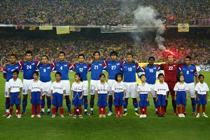 11 members of the Malaysian football team standing side-by-side on the field of a stadium