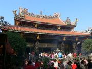 A temple decorated by dragons and other mythical animals. People are gathered in front of it and some of them are praying.
