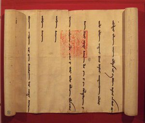 A partially unrolled scroll, opened from left to right to show a portion of the scroll with widely spaced vertical lines in the Mongol language. Imprinted over two of the lines is an official-looking square red stamp with an intricate design.