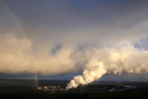 A rainbow is to the left, as a plume of volcanic ash drifts to the right.