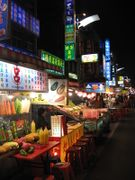A picture showing market food stalls by night.