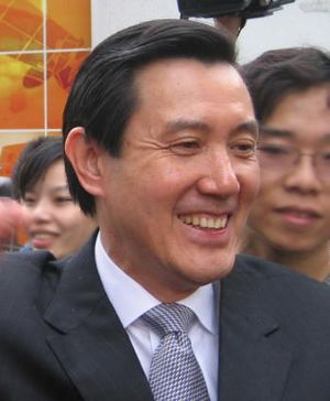 An East Asian man in suit smiling to the crowd